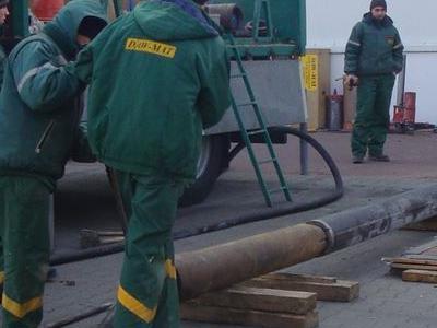 pracownicy w zielonych strojach przy samochodzie