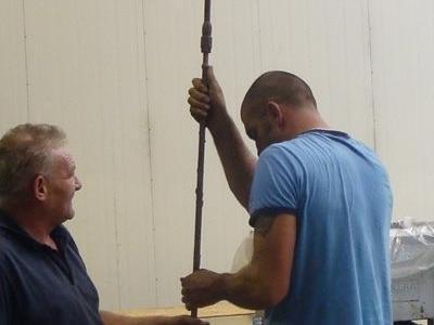dwóch mężczyzn sprawdzających głębokość dziury w hangarze
