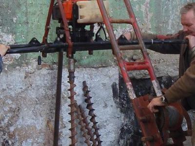 mężczyźni  trzymający maszynę w ziemi