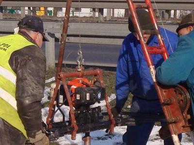 3 mężczyzn sterujących maszyną do wykopywania dziury w ziemii02