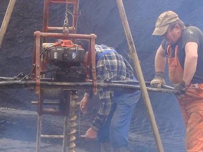 3 mężczyzn sterujących maszyną do wykopywania dziury w ziemii